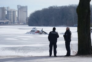 Berlin, Germany. Police look out toward a motorboat lying partially capsized in the frozen Spree River, near Rummelsburg district
