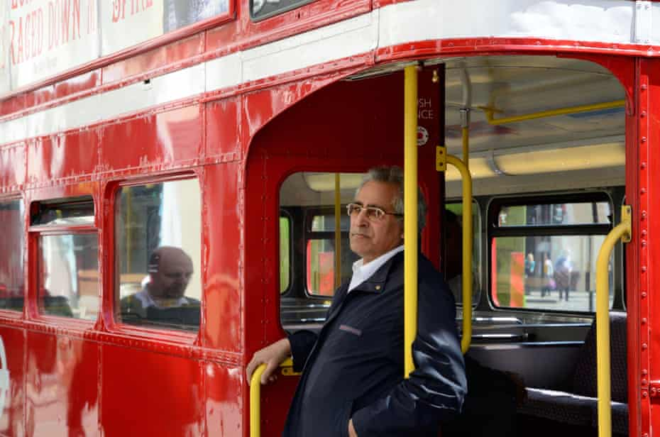 A conductor hangs on to the pole at the back of an old Routemaster. TfL could not afford conductors on each bus, and the 'hop on, hop off' element of the new routemasters was designed out.