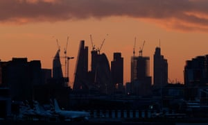 The sun sets behind the skyline of the City of London.