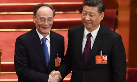 Wang Qishan, left, shakes hands with Xi Jinping after being elected vice president.