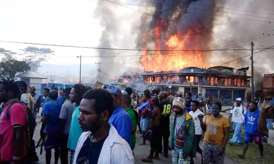 Protesters in West Papua with burning buildings