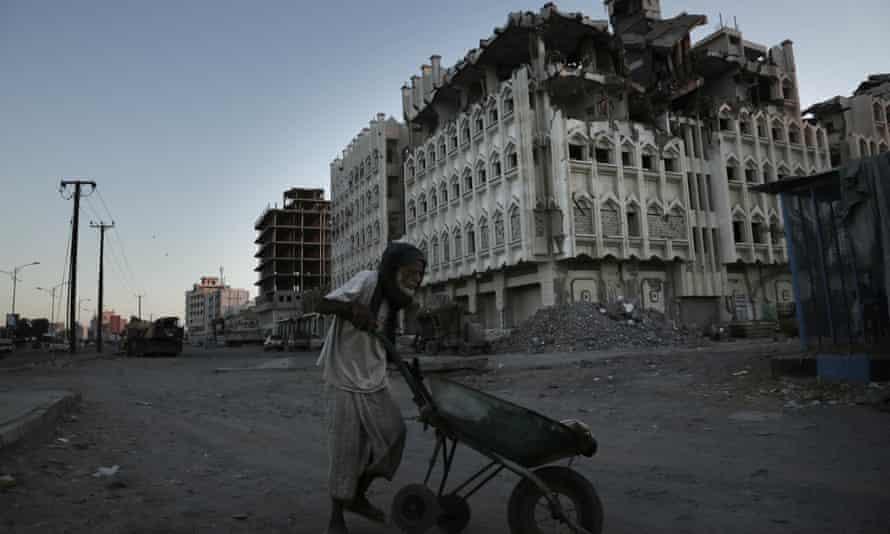 A man walks past a damaged building in Aden, Yemen