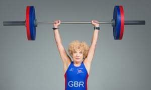 Edwina Brocklesby, 74, the country's oldest ultra-distance triathlete, wearing a GBR vest and holding a weight-lifting bar above her head