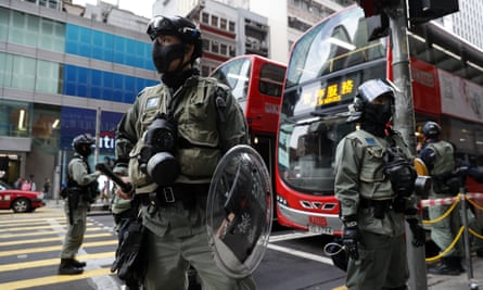 Police stand guard in front of a bus stop in Hong Kong.