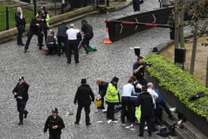 A policeman points a gun at a man on the floor at the top of the frame as emergency services attend the scene outside the Palace of Westminster