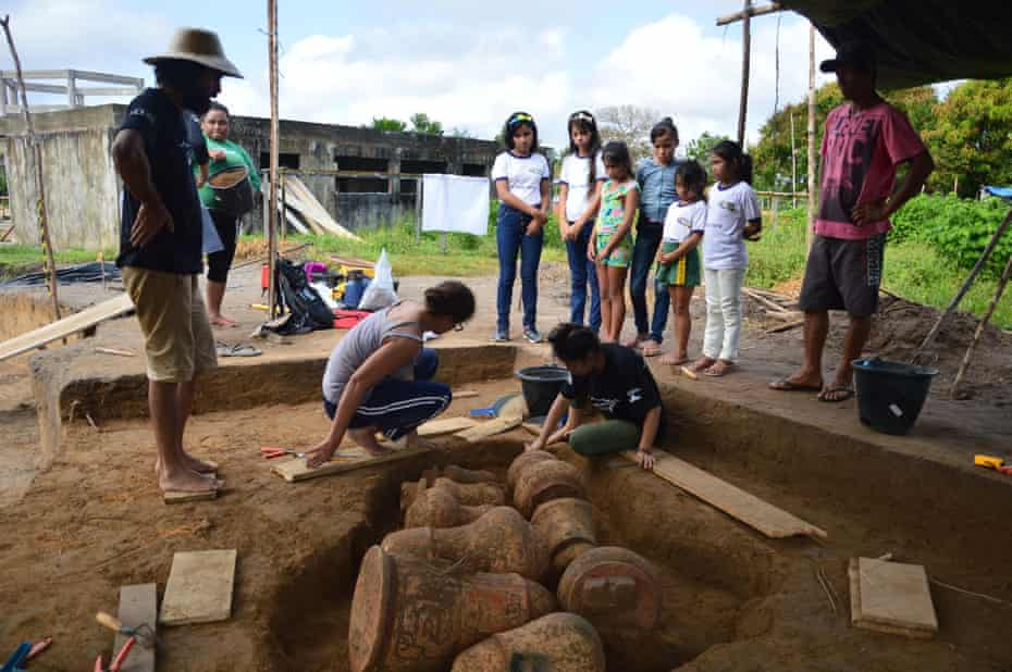 Archaeologist unearth urns buried near from the community school in Tauary, in the Brazilian Amazon.