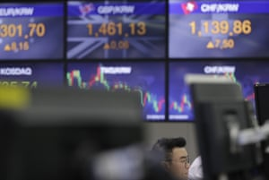 A currency trader watches the computer monitors near the screens the foreign exchange rates at the foreign exchange dealing room in Seoul, South Korea.
