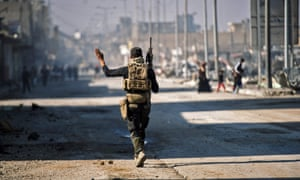 A member of the Iraqi special forces patrols a street in eastern Mosul.