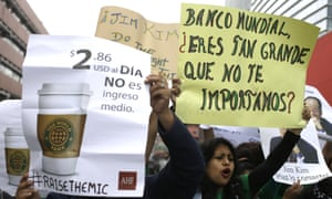 Demonstrators hold messages near the site where the International Monetary Fund is holding its annual meeting in Lima, Peru.