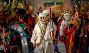 Tibetan monks dressed as demons attend the Beating Ghost festival in Beijing. A top minister has chastised officials for believing in ghosts and gods.