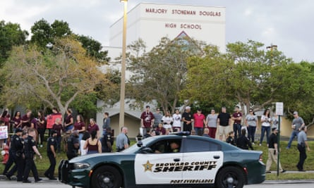 A police car drives by Marjory Stoneman Douglas high school in Parkland, Florida, as students return to class.