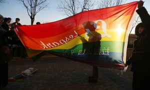 Supporters of China's lesbian, gay, bisexual and transgender community unfurl a rainbow flag outside a court in Beijing