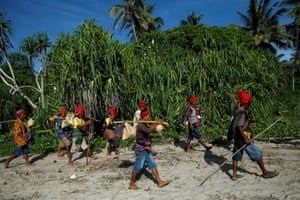 East Nusa Tenggara, Indonesia. Sumba priests carry crops and goods after attending a ritual during the Pasola festival, an ancient annual ritual to welcome the new harvest season