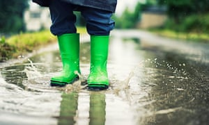 Closeup of galoshes splashing in a puddle.