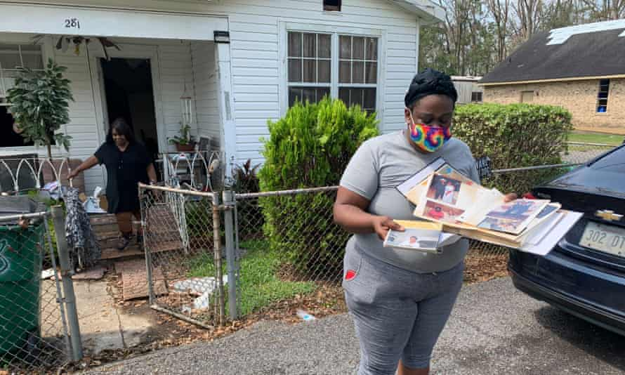 Gayle Robinson holds family photo albums outside her mother's destroyed home in Mount Airy, Louisiana