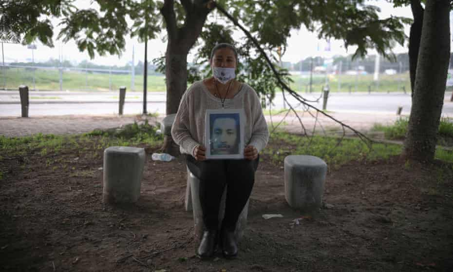 A woman holds a portrait of a missing relative.