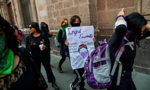 A woman holds a sign for Ingrid Escamilla as women demonstrate outside the national palace in Mexico City on 14 February.