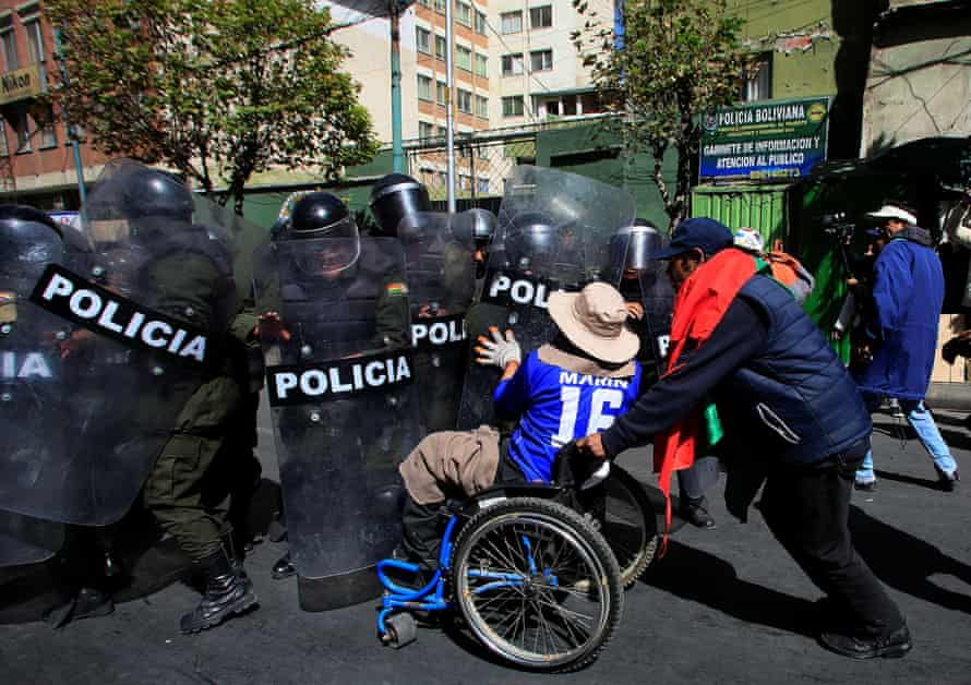A demonstrator with a physical disability tries to pass a riot police barricade in El Alto, Bolivia.