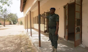 A police officer stands guard at the premises of Government Girls' Science and Technical College, where 110 girls were kidnapped by Boko Haram.