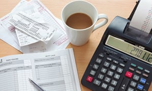 Still life bookkeeping photo of a sales ledger with a pile of receipts, invoices and a print calculator.