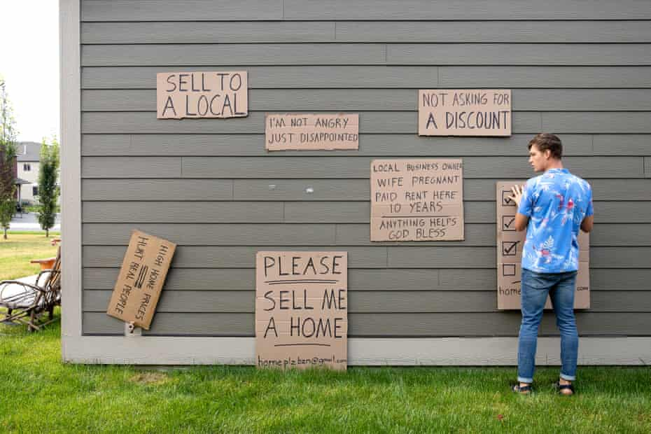 Sean Hawksford hangs the signs he used to find someone willing to sell him a house.