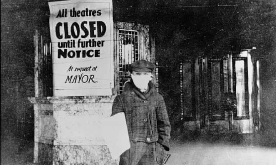 A man wearing a mask stands beside a poster reading: 'All theatres closed until further notice at request of the mayor'