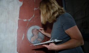 A restorer works on a fresco inside the House of the Bicentenary