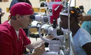 Rand Paul examines the eyes of Natanaelle Jean Louis, 9, during a cataract surgery clinic in Cap-Haitien, Haiti.