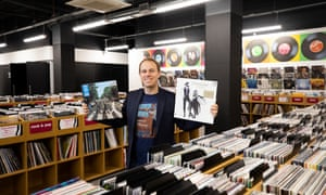 The owner of HMV, Doug Putman, in a store holding up a Beatles vinyl and a Fleetwood Mac vinyl