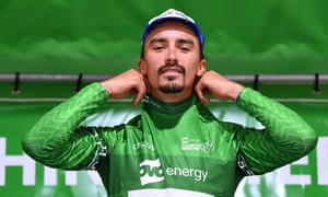 Julian Alaphilippe tries on the leader's green jersey.