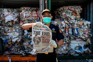 Surabaya, Indonesia: A customs officer holds up a newspaper from a container filled with trash coming from Australia. It should have contained only waste paper but authorities also found hazardous material