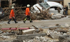 Emergency workers walk past a car smashed against a building in Braunsbach, where a river broke its banks. Photograph: Sean Gallup/Getty Images