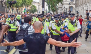 London, UK: police make an arrest in Whitehall during a protest against Covid vaccinations, passports and restrictions, with many demonstrators calling the pandemic a 'hoax'