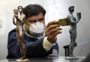 Burbank, US. Foundry worker Ricardo Gortinez applies a blue-green patina to an Actor statuette in preparation for the Screen Actors Guild Awards later this month