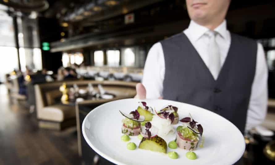 A waiter holds a tuna starter at the City Social Restaurant