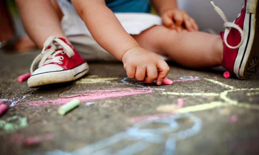 Close up of boy in canvas shoes drawing with chalks on the sidewalk
