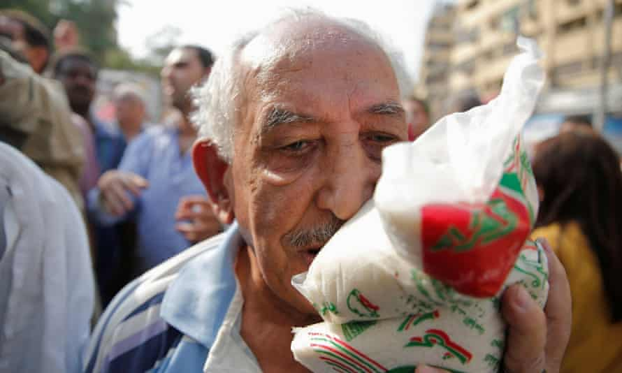 A man carries sugar bought from a government truck in Cairo, where it has all but vanished from supermarkets.