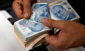 A money changer counts Turkish lira banknotes at a currency exchange office in Istanbul.