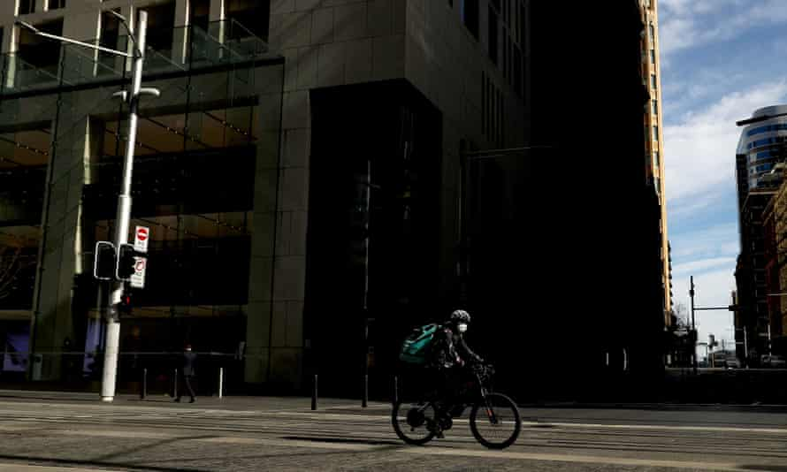 A food delivery cyclist rides through the quiet streets of Sydney's CBD during the city's lockdown. A public health specialist says NSW should introduce stricter measures to control the Covid-19 outbreak faster.
