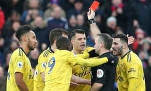 Paul Tierney shows Pierre-Emerick Aubameyang a red card after VAR upgraded a yellow card he received for a foul on Max Meyer.