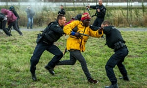 French gendarmes try to stop migrants on the Eurotunnel site in Coquelles near Calais.