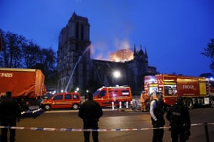 French firefighters try to extinguish a fire as flames are burning the roof of the Notre Dame Cathedral in Paris.
