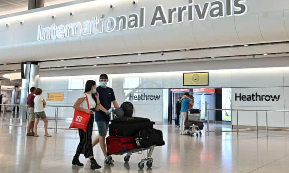 Passengers walk through the arrivals hall after landing at Terminal Two of Heathrow airport in London.