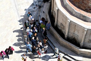 Tourists listen to their guide on the Stradun