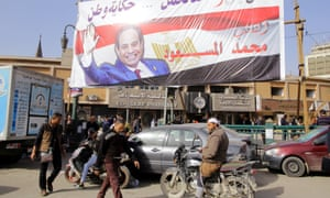 People walk underneath an election campaign banner for Abdel Fatah al-Sisi in Cairo.