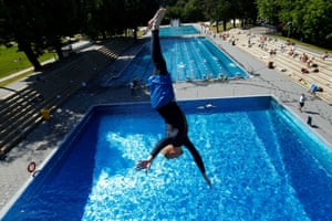 A swimmer dives into the water as a public open-air pool reopens in Cologne, Germany