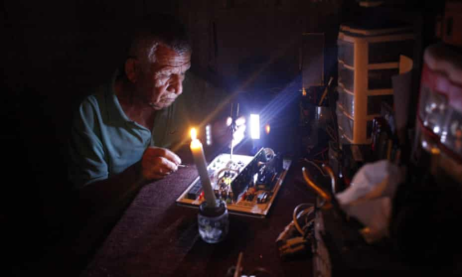 A man repairs an electronic device during a power cut in San Cristobal.