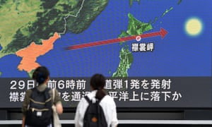 Pedestrians in Tokyo watching the news on a huge screen covering the launch of a missile by North Korea that flew over Japan.
