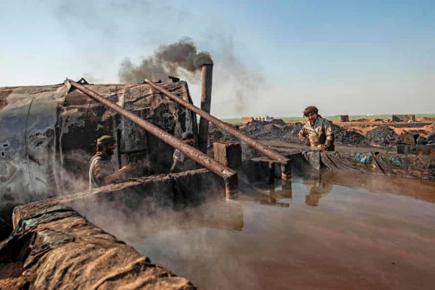 Men work at a primitive oil refinery in countryside outside al-Qahtaniyah, a town in Syria's north-eastern Hasakeh province