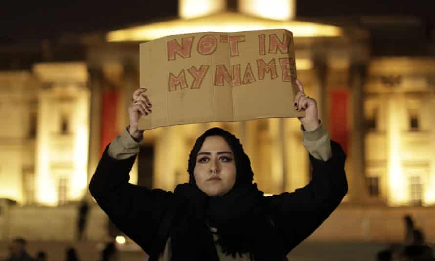 A woman holds a sign at the vigil, called to show solidarity with the victims and their families.